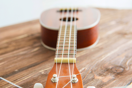 Photo depicts musical instrument ukulele guitar on a wooden table 版權商用圖片