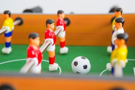 Juego de futbolín con jugadores amarillos y rojos y portero blanco. Juego de futbol de mesa.