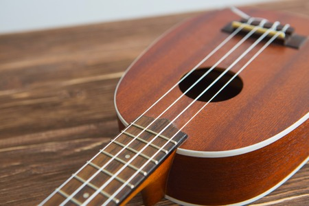 Photo depicts musical instrument ukulele guitar on a wooden table Фото со стока
