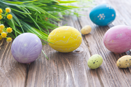 Easter eggs and spring flowers on an old wooden background.