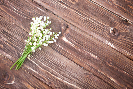 Wonderful fragrant white flowers with a delicate scent. Beautiful lily of the valley bouquet on wooden background, top view. Space for text