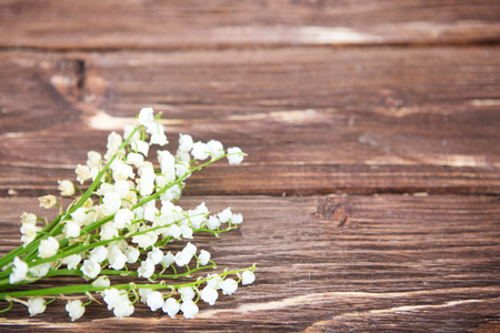 Wonderful fragrant white flowers with a delicate scent. Lilies of the valley on a brown rustic wooden background