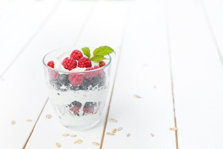 layered dessert with raspberry cream cheese in glass on a white wooden table. Imagens - 122968344