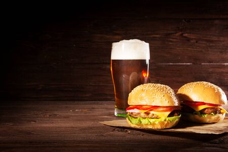 Hamburger and dark beer in vintage wooden table