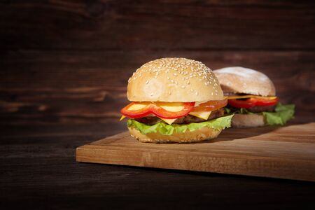 Two hamburgers on a wood board over rustic background