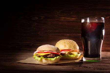 Two BBQ hamburgers with cola on wooden surface background. 写真素材