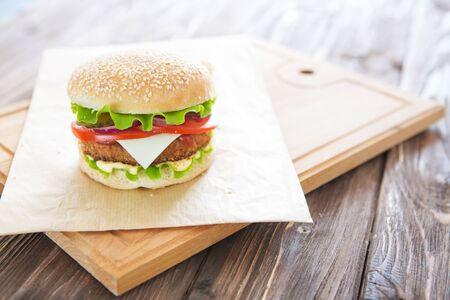 Delicious fast food. Homemade, beef hamburger with cheese and vegetables. Stock Photo