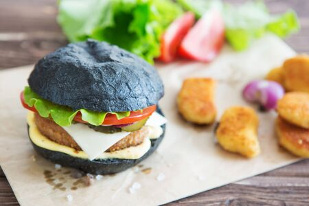 Delicious fast food. Black burger on the wooden serving tray. 版權商用圖片