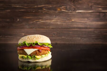 Delicious fast food. Juicy cheeseburger on the wooden background