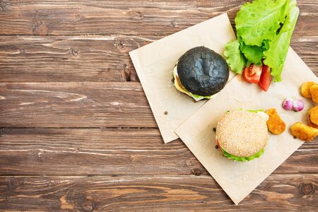 Delicious fast food. Craft beef burgers with vegetables. Flat lay on wooden textured background with sesame seeds. Stock Photo