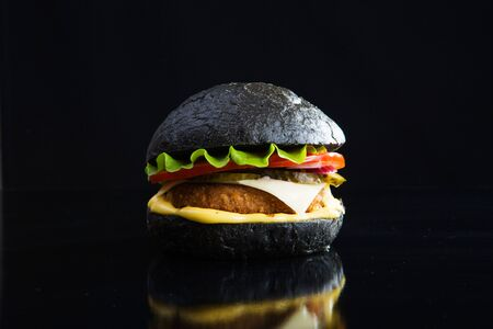 Delicious fast food. Modern black burger on black bacground. Toned picture