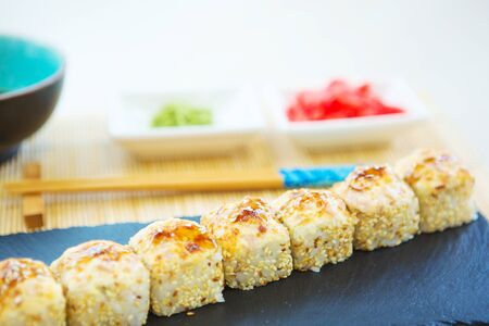 Maki Sushi - Rolls with Fried Salmon and Cream Cheese insisde. Cucumber outside. Topped with Salmon Caviar Healthy and tasty food. Stock Photo