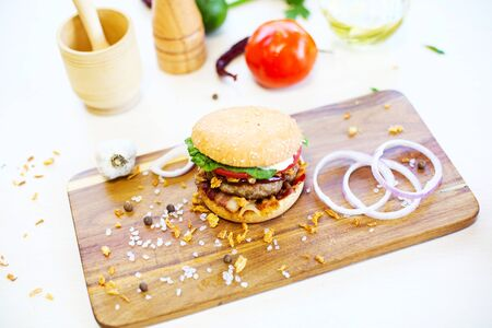 Homemade burger with beef, fried bacon and onion on wooden cutting board. Healthy and tasty food.