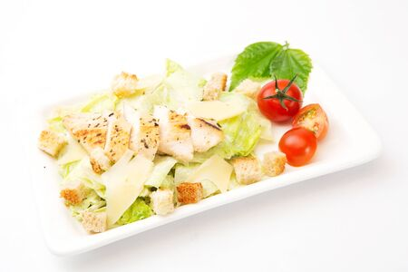 Homemade Vegetable salad with chicken and cheese on white rectangular plate on white background. Healthy and tasty food. Stock Photo