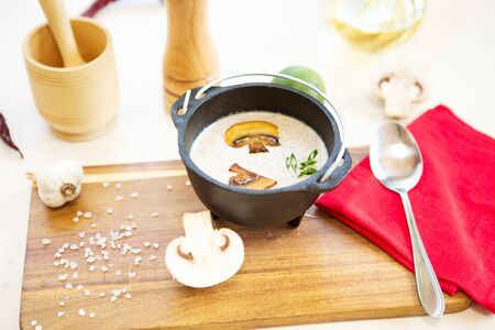 Bowl with mushroom cream soup decorated with sliced champignons. Healthy and tasty food.