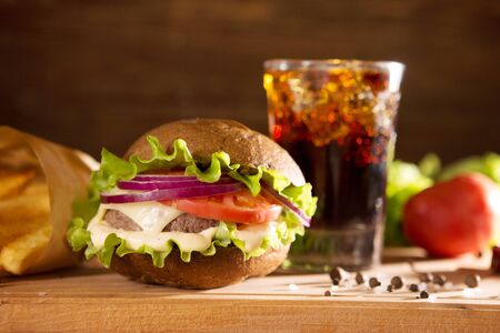 american snack with big burger and glass cola on wooden table Delicious fast food. 免版税图像