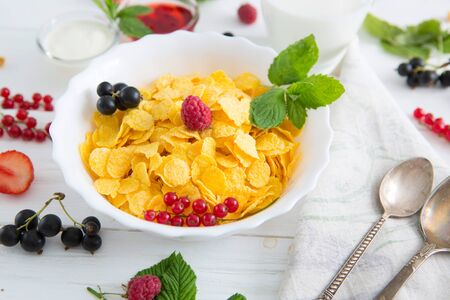 Muesli with berries and milk Healthy tasty breakfast cornflakes with strawberries, raspberries, black currants and red currants.