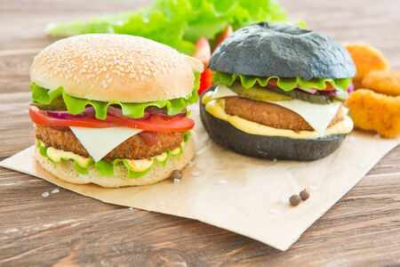 Delicious fast food. Two hamburgers with beef burger cutlet, fried onion, spinach, ketchup sauce and blue cheese in traditional buns, served on wood chopping board over dark wooden background. 免版税图像