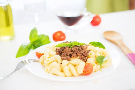 Penne in bolognese and tomato sauce with basil on top.