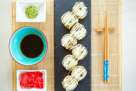 Plate of tempura maki sushi rolls with cream cheese, avocado and tuna at decorated with flowers table background. Healthy and tasty food.