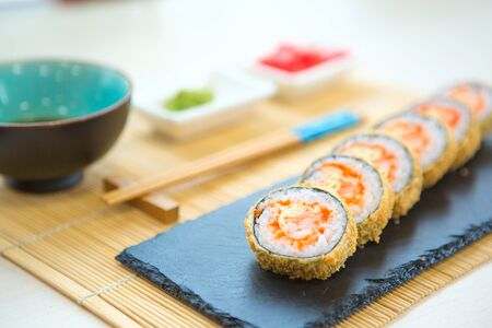 fried rice cover sushi rolls on black table, sea food Healthy and tasty food. Stock Photo