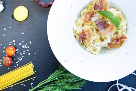 Pasta with tomato sauce and bacon on a black stone surface Healthy and tasty food. Stock Photo