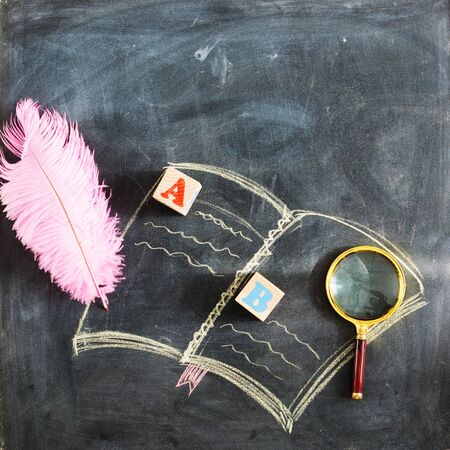 Back to school. Drawing of a book on a school blackboard with school supplies and a magnifier and an empty place for your text or design.