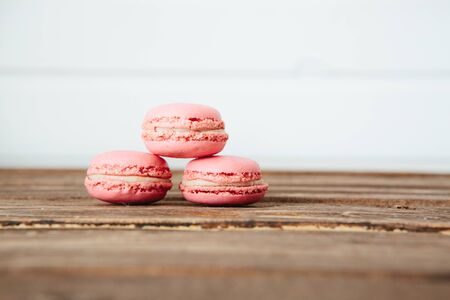 Sweet colorful French macaroon cookies dessert on brown wooden table over white wooden background Zdjęcie Seryjne - 129211353