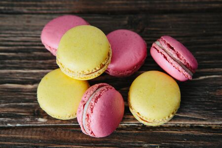 Sweet colorful French macaroon cookies dessert on brown wooden table