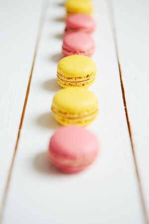 Sweet colorful French macaroon cookies dessert on white wooden table