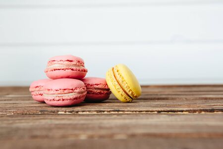 Sweet colorful French macaroon cookies dessert on brown wooden table over white wooden background Zdjęcie Seryjne - 129211804