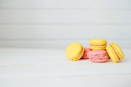 Sweet colorful French macaroon cookies dessert on white wooden table Zdjęcie Seryjne - 129211225