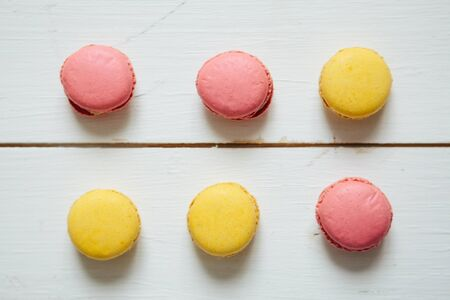 Sweet colorful French macaroon cookies dessert on white wooden table Zdjęcie Seryjne - 129211232