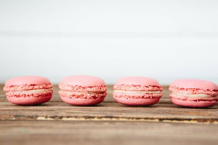 Sweet colorful French macaroon cookies dessert on brown wooden table over white wooden background Zdjęcie Seryjne - 129211231