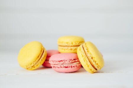 Sweet colorful French macaroon cookies dessert on white wooden table Zdjęcie Seryjne - 129211254