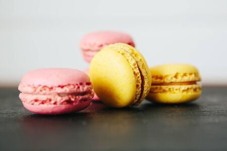 Sweet colorful French macaroon cookies dessert on black stone surface over white wooden background