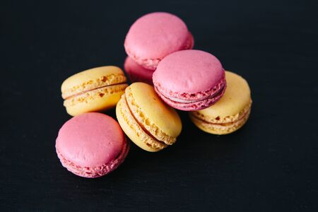 Sweet colorful French macaroon cookies dessert over black background