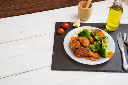 Fried vegetables broccoli, mushroom and carrot on white plate with chicken meat on brown wooden table. Stock fotó