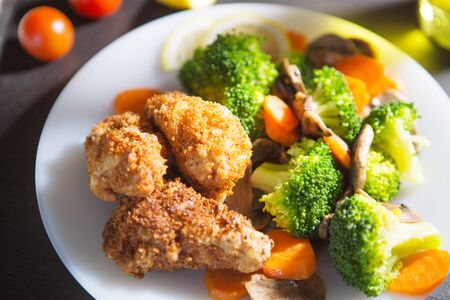 Grilled fIllet of chicken garnished with broccoli, carrots and mushrooms.