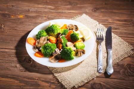 Delicious vegetarian food in a dish vegetable meal. Broccoli, carrots and mushrooms.