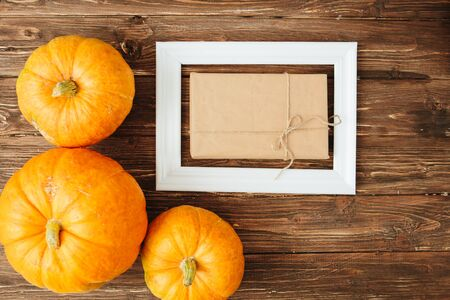 Pumpkins with white frame for picture and brown paper package tied up with strings inside over wooden background. Thanksgiving and Halloween concept. View from above. 스톡 콘텐츠