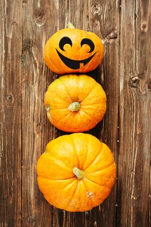 Pumpkin snowman on a wooden background with a jack-o-larten face Thanksgiving and Halloween concept. View from above. Top view. Vertical image for smartphone