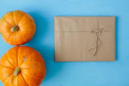 Orange pumpkins with gift in brown paper package tied up with strings on blue wooden background Thanksgiving and Halloween concept. View from above. Top view. Copy space for text and design
