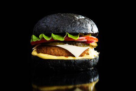 Restauration rapide délicieuse. Burger noir moderne sur fond noir. Image tonique