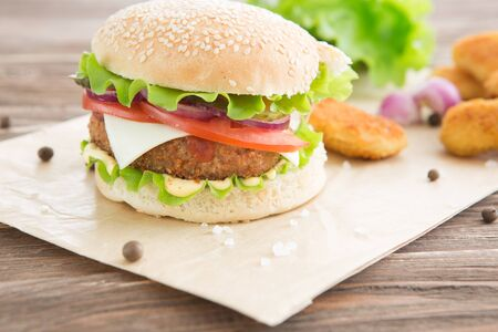 Delicious fast food. Cheese burger with grilled meat, cheese, tomato, on craft paper on wooden surface. Fast food template. Real photo. ideal for advertisement