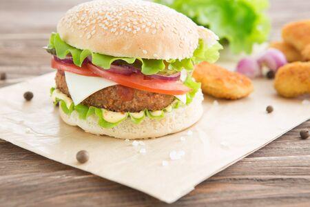 Restauration rapide délicieuse. Burger au fromage avec viande grillée, fromage, tomate, sur du papier kraft sur une surface en bois. Modèle de restauration rapide. Vrai photo. idéal pour la publicité