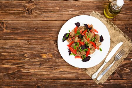 Fried liver with onion and tomatoes on wooden background.