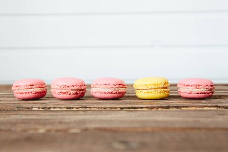 Sweet colorful French macaroon cookies dessert on brown wooden table over white wooden background