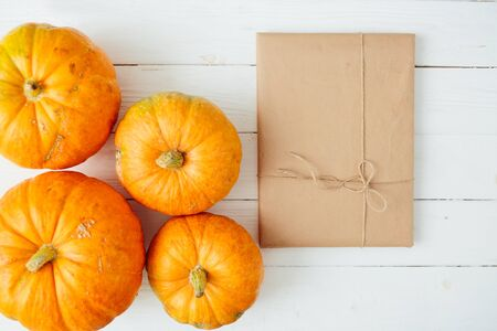 Top view of orange Pumpkins with gift in brown paper package tied up with strings on old wooden background. Thanksgiving and Halloween concept. Copy space for text and design