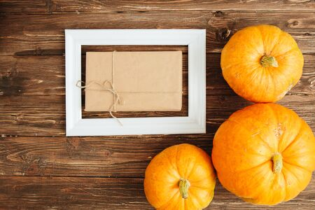 Orange Pumpkins with white frame for picture and brown paper package tied up with strings inside over wooden background. Thanksgiving and Halloween concept. View from above. 스톡 콘텐츠